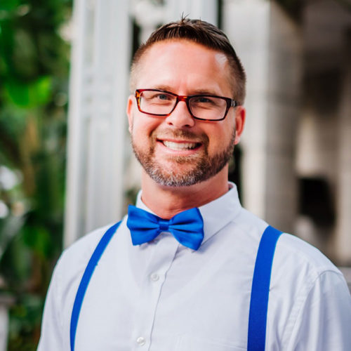 Jason- man smiling with glasses wearing a white button down, blue suspender and blue bow tie