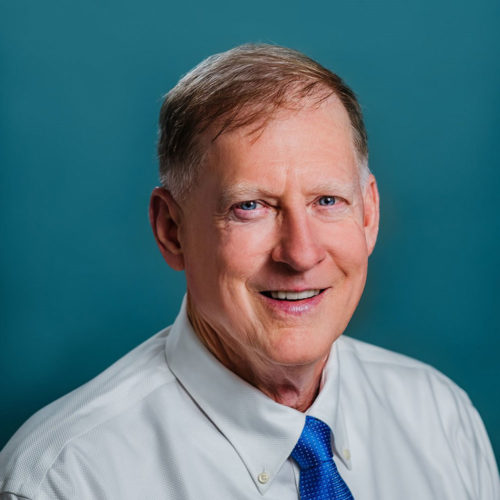 Dr. Jacobs- older man smiling wearing a white button down and royal blue tie